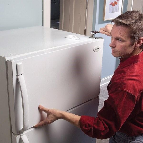 Мастер диагностирует холодильник